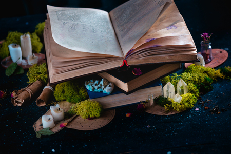 Open book with candles, crystals, and moss. Reading fantasy concept with copy space. Magical still life on a dark background with occult equipment.