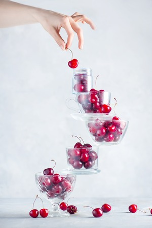 Cherry on top of a balancing stack of bowls and cups filled with berries. Final touch concept on a white background with copy space 写真素材