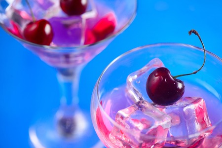 Cherry cocktail close-up. Martini glass with ice cubes and cherries on a bright blue background with copy space. Hot summer day refreshment concept Stock Photo