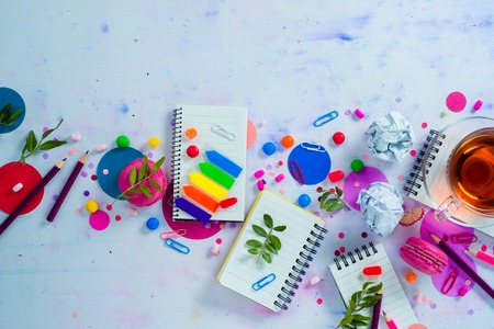 Colorful notebook with pencils and confetti on a light background with copy space. Pink and purple palette still life. Easy lifestyle concept