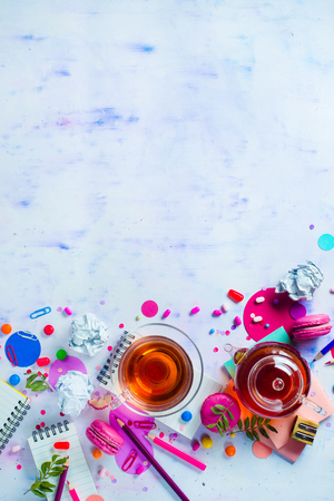 Tea party with a tiny glass teapot, candies, and confetti on a light background with copy space. Pink and purple palette still life. Vibrant drinks concept