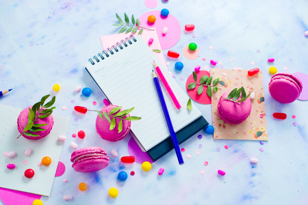 Party flat lay with confetti. To-do list with stationery, candies and macaroon cookies on a white wooden background. Colorful objects in high key with copy space. Stock Photo