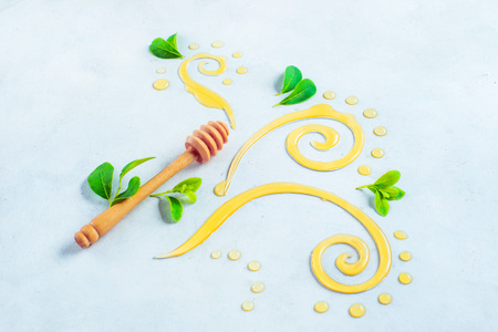 Decorative honey swirls and lemon slices header. Honey dipper on a white background with copy space. Painting with food concept. Creative food photography