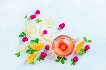 Honey and tea header. Glass teapot with decorative honey swirls, lemon slices and green leaves. Home remedies flat lay on a white background with copy space