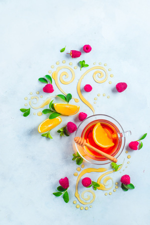 Honey tea from above. Decorative honey swirls, lemon slices, berries and tea in a glass cup on a white wooden background with copy space. Creative food flat lay