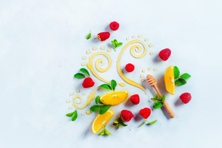 Honey dipper on white background with berries and lemon slices. Decorative honey swirls with green leaves. High key flat lay with copy space