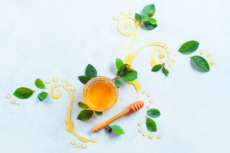 Honey dipper and a glass jar with decorative honey swirls and green leaves on a white background with copy space. Creative food flat lay. Painting with food concept