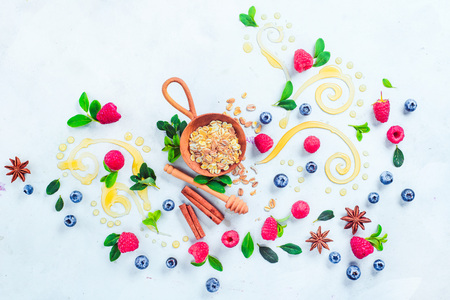 Oatmeal with honey, cinnamon, and berries. Raw ingredients with decorative honey swirls on a white wooden background with copy space