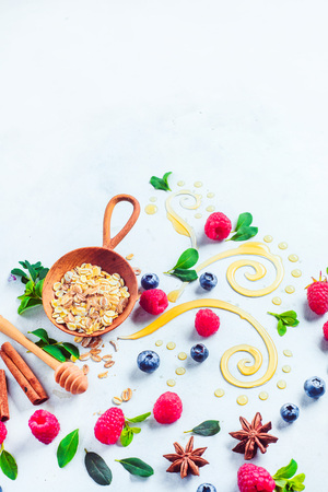 Oatmeal porridge ingredients on a white wooden background. Granola, honey, cinnamon, and berries with copy space