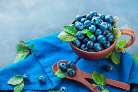 Blueberries in a ceramic cup with wooden spoons and a linen napkin. Ripe and sweet summer berries on a stone background. Neutral colors, blue and gray palette, copy space