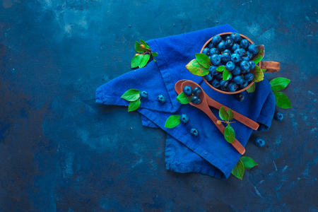 Summer berry harvest concept on a dark blue background with copy space. Blueberries in a ceramic cup flat lay. Top view food photography Standard-Bild