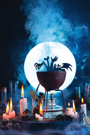 Halloween concept with a cauldron silhouette in front of full Moon. Magical potion with rising steam on witch or wizard workplace. Conceptual still life on a dark background with copy space.