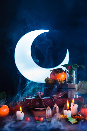 Halloween persimmon with shining full Moon. Witch or wizard workplace with burning candles. Spooky still life concept on a dark background with copy space.