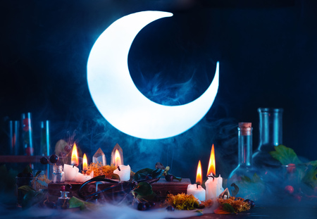 Halloween header with shining full Moon. Witch or wizard workplace with burning candles. Spooky still life concept on a dark background with copy space.