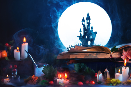 Halloween concept with a haunted castle silhouette in front of full Moon. Book of spells on witch or wizard workplace. Creative magical still life on a dark background with copy space.