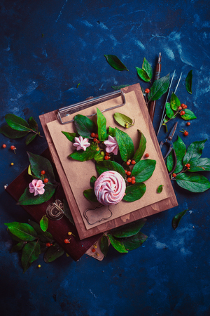 Floral arrangement with meringues or marshmallow. Tree branch with green leaves and berries on a wooden clipboard. Modern dessert concept