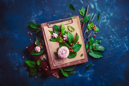 Meringues or marshmallow in a flower bouquet on a wooden clipboard Tree branch with green leaves and berries on a wooden clipboard. Modern dessert concept