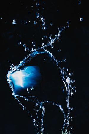 Dynamic splash of water on a dark background. Flying transparent liquid with a shiny surface. High-speed explosion photography.