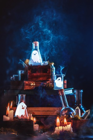 Little ghosts in glass jars. Halloween concept on a dark background with a stack of magical books and mysterious smoke.