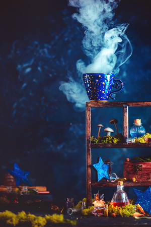 Ceramic cup with constellations and rising steam on a shadow case with mushrooms and crystals. Witch or wizard workplace with copy space. Standard-Bild