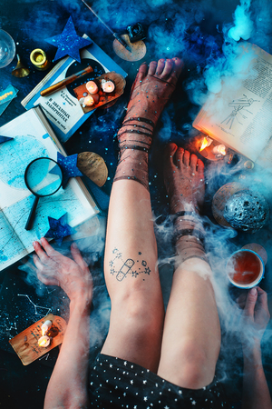 Astronomy hobby flat lay with young women legs, books, stars, and smoke on a dark background with copy space Standard-Bild