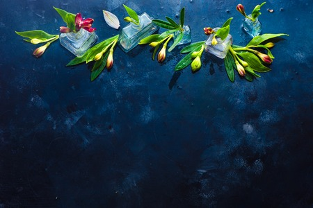 Flowers in tiny glass bottles on a dark wet background with copy space. Alstroemeria floral header for a flower shop.