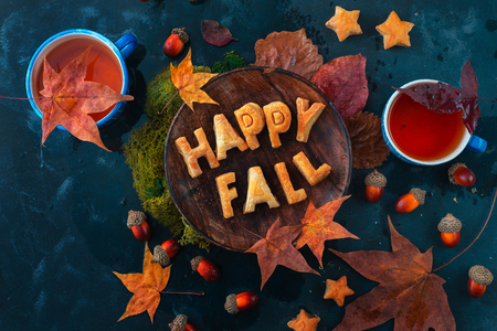 Happy fall food lettering made with cookies. Autumn flat lay with tea, sweets and fallen leaves on a dark background with copy space Standard-Bild