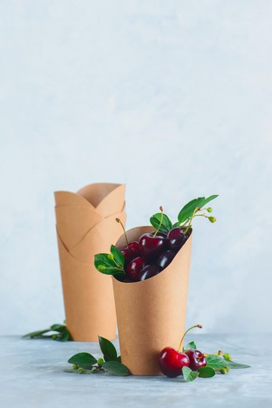 Craft paper eco-friendly food packaging with cherries. Disposable cups on a neutral gray background with copy space. Preserving nature and recycling concept. Standard-Bild