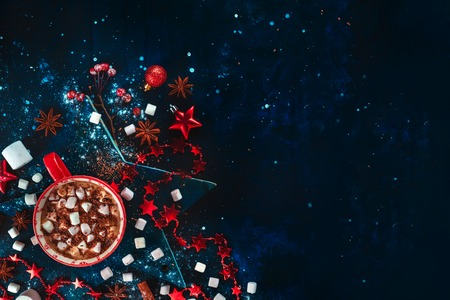 Hot chocolate Christmas flat lay with copy space. Red mug on a star-shaped coaster with mini marshmallow, cinnamon, and New Year decorations. Low key drink photography Standard-Bild