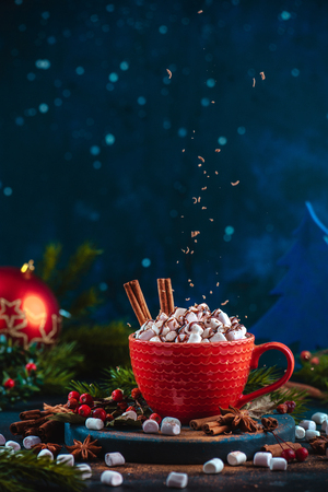 Hot chocolate with marshmallows, chocolate crumbs, and syrup. Large coffee cup with homemade cocoa. Christmas drink photography on a tinted background