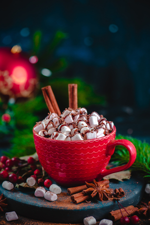 Christmas hot chocolate close-up with marshmallows, chocolate crumbs, and syrup. Large coffee cup with homemade cocoa. Winter drink photography on a dark background Standard-Bild