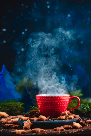 Christmas hot drink with rising steam, cinnamon, and star-shaped cookies. Large coffee cup with homemade cocoa. Winter drink photography on a dark background