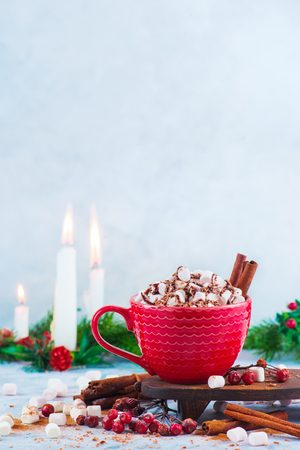 Hot chocolate with marshmallows, chocolate crumbs, and syrup on a white background with copy space. Modern Christmas concept. Winter drink photography