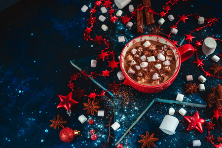 Hot cocoa winter flat lay. Red mug of Christmas chocolate on a star-shaped coaster with mini marshmallow, cinnamon, and decorations. Dark background with copy space