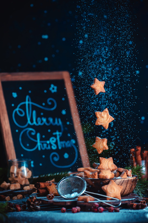 Flying star-shaped cookies with sugar powder and Merry Christmas lettering. Traditional baking concept on a dark background with copy space Standard-Bild