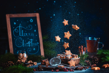 Flying star-shaped cookies with sugar powder and Merry Christmas lettering. Traditional baking header on a dark background with copy space