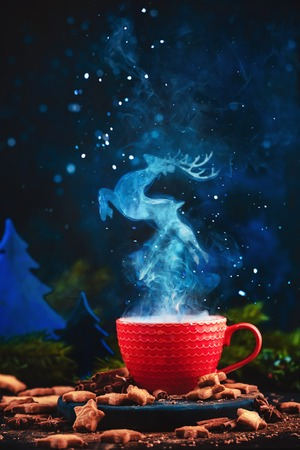 Reindeer figure in a steam over a cup of hot winter drink. Christmas tale concept on a dark background with copy space 写真素材