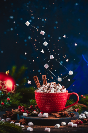Marshmallow Ursa Major constellation with chocolate crumbs over a red cup of Christmas hot chocolate. Winter drink on a dark background with copy space. Action food photo