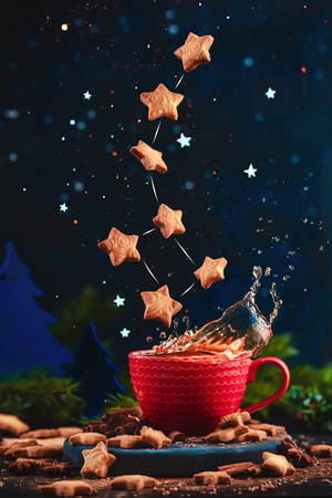 Star-shaped cookie Ursa Minor constellation with chocolate crumbs over a red cup of Christmas hot chocolate. Winter drink on a dark background with copy space. Action food photo