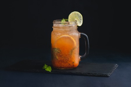 Ice cold citrus cocktail in a vintage glass mason jar. Dark background with copy space for a menu.
