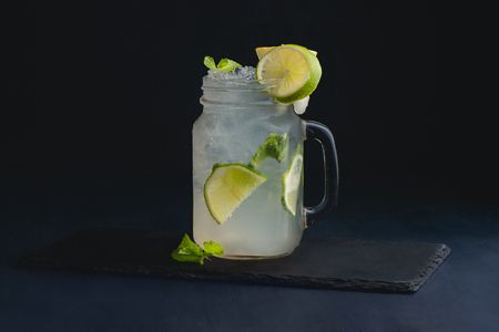 Ice cold classic lime lemonade in a vintage glass mason jar. Dark background with copy space for a menu. 写真素材