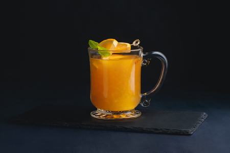 Fruit punch in a glass cup on a dark background with copy space for a menu. Orange, sea buckthorn or mango winter drink 写真素材