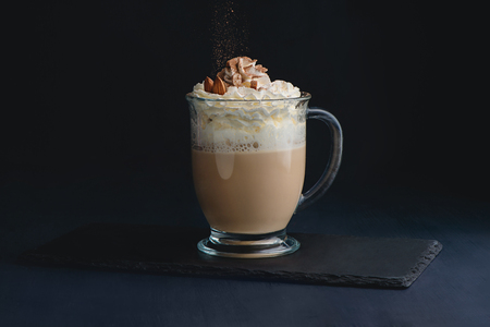 Coffee and milk latte drink with whipped cream, nuts and cocoa powder. Sweet hot drink on a dark background with copy space for a menu