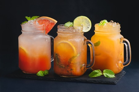A variety of citrus cocktails vintage glass mason jars with mint and grapefruit. Dark background with copy space for a menu.