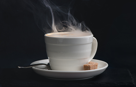 Steaming hot cup of coffee on a dark background with copy space