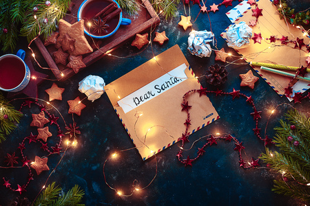 Letters to Santa concept, Christmas flat lay with fairy lights, star-shaped cookies, and tea. Christmas still life from above with contrast colors and copy space