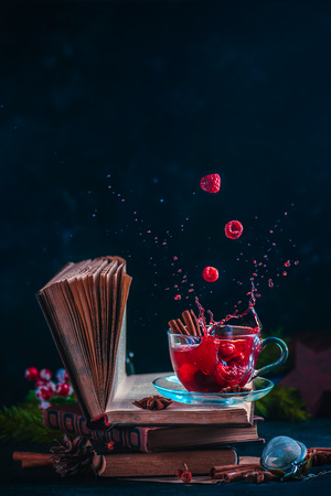 Red berry tea on a stack of books with a dynamic splash. Winter hot drink on a dark background with copy space 写真素材