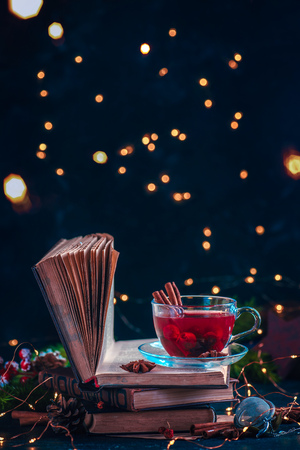 Red berry tea on a stack of books with fairy lights. Christmas drink on a dark background with copy space