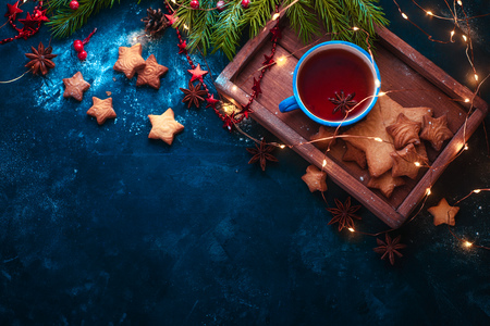 Cookies, tea and fairy lights flat lay with fir tree branches, wooden tray, anise stars, and decorations. Warm winter concept with copy space 写真素材