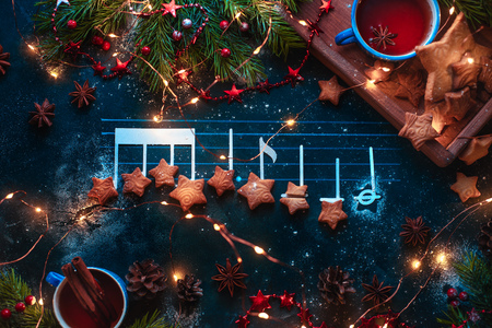 Christmas melody notes flat lay with star-shaped cookies, fir tree branches, wooden tray, anise stars, and decorations. Christmas carol concept for a header or postcard 写真素材